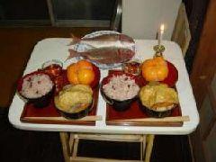 魚(鯛)や小豆飯や柿、油揚げが載った野菜の煮物を供える