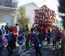子どもたちが曳く山車(屋台)。上部にはお囃子の子供たちが乗っている