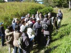 相原古窯跡群で、参加者の真ん中で説明する調査会会員。多くの人がいるがこれでも参加者半分への説明