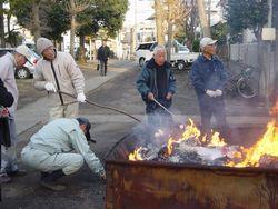 ⑬住宅地中の杉山神社敷地で行うため燃やすものを高く積んだりせず、団子焼きにも順次、焼く人が訪れる(町田市金森)