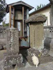 今泉の陽石道祖神。手前の庚申塔の前には「ケズリカケ※」が供えられている  ※木を削って花のような形にしたもの