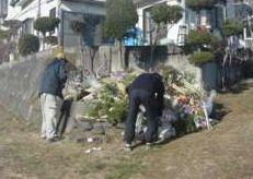 石碑の前に納められた お飾りを運ぶ